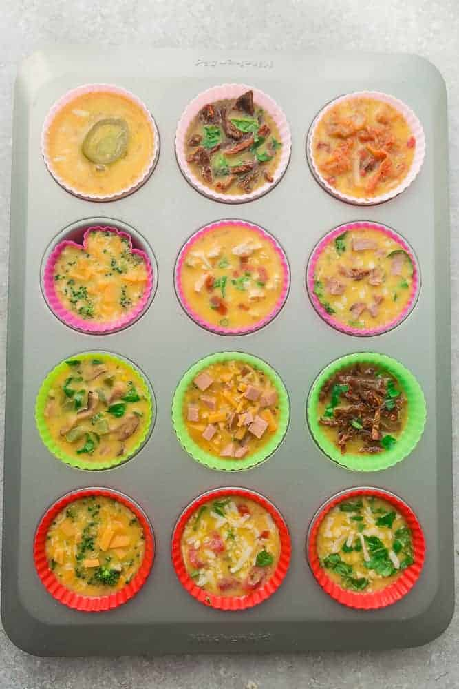 12 Silicone Liners in a Muffin Tin Filled with the Batter for Various Muffin Flavors