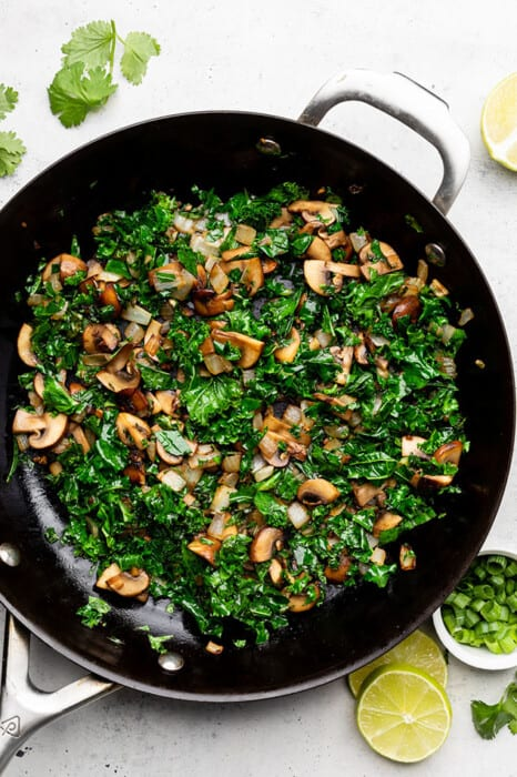Overhead view of diced mushrooms, onions and shredded kale in a skillet