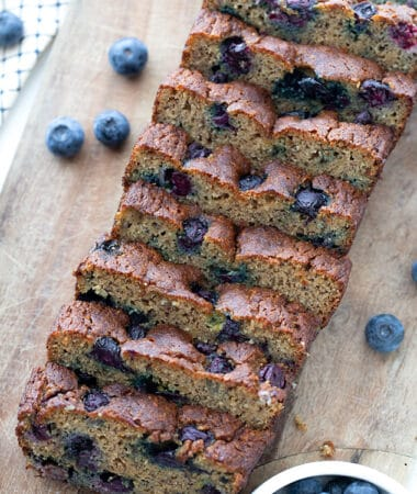 Top view of 8 slices of blueberry banana bread on a cutting board