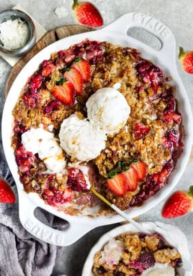 Top view of baked healthy strawberry rhubarb crisp in a white pie pan with coconut ice cream and a spoon