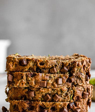 Side view of four stacked zucchini banana bread slices on a white background