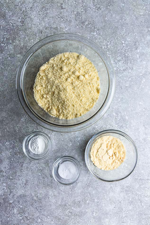 Dry ingredients to make cake in a four separate clear mixing bowls