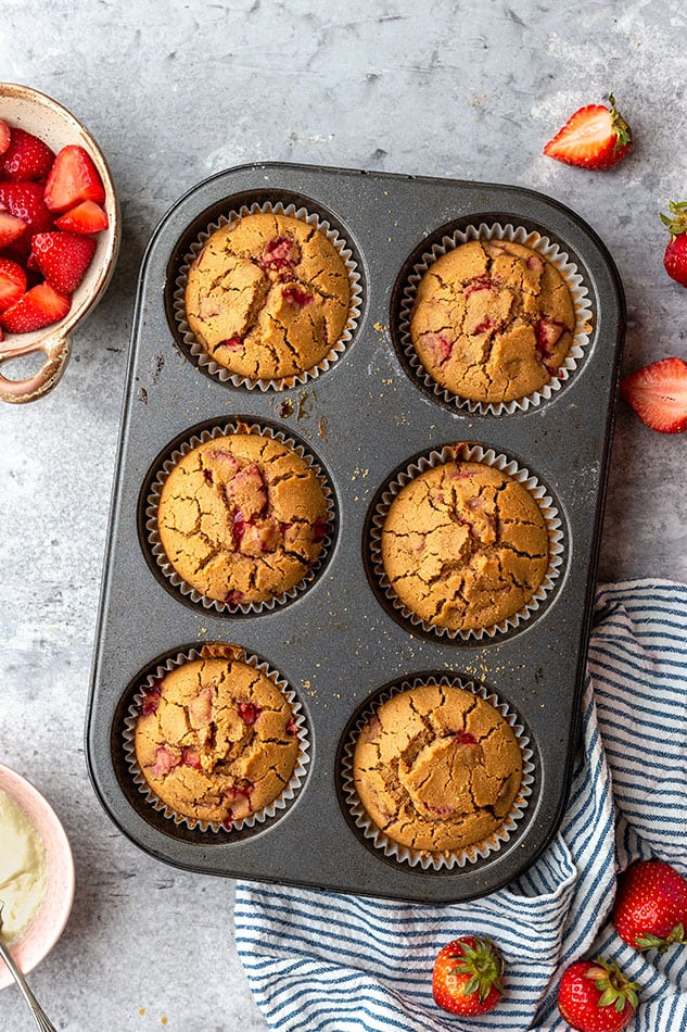 Overhead image of six strawberry muffins in muffin tin.