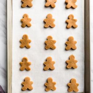 Top view of 15 cut-out keto gingerbread cookie dough on a baking sheet