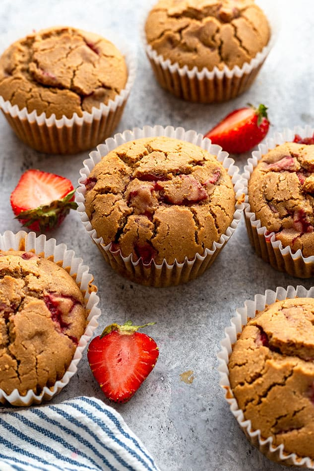 Side view of strawberry muffins on grey surface with fresh strawberries.