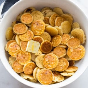 Top view of mini pancake cereal in a white bowl with a square of butter and maple syrup