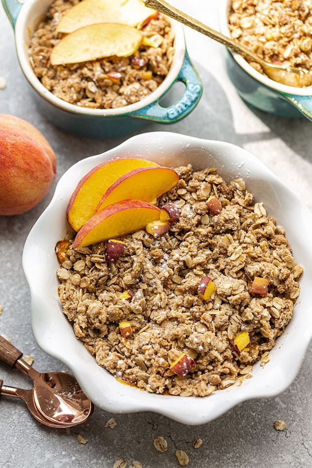 View of peach crisp in white bowl with fresh peaches.
