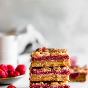 Side view of three raspberry crumb bars stacked on a white background