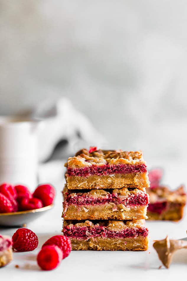 Front view of stack of three raspberry crumb bars on white surface.