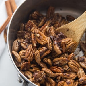 Top view of cinnamon roasted pecans in a pot with a wooden spoon