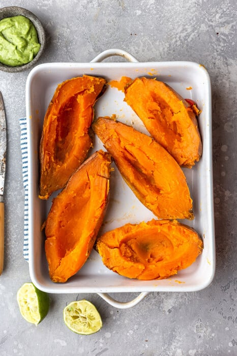 Five Halved Sweet Potatoes in a Pan Beside a Small Dish of Avocado Sauce