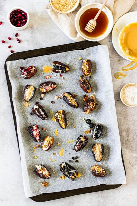 Top view of scattered traditional stuffed dates on a baking sheet