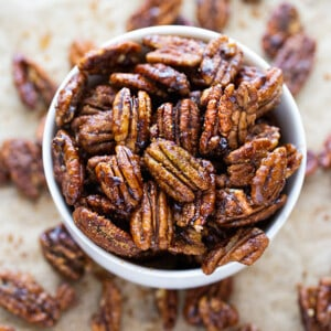 Top view of a pile of easy candied pecans in a white bowl