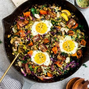 Top view of sweet potato hash with bacon and eggs in a cast-iron skillet on a grey background