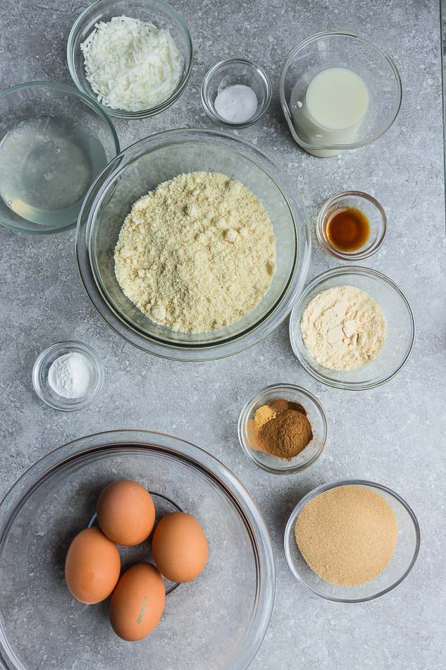 Top view of baking ingredients in glass bowls on grey surface.