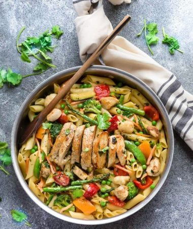 Top view of pasta primavera topped with sliced chicken in a skillet