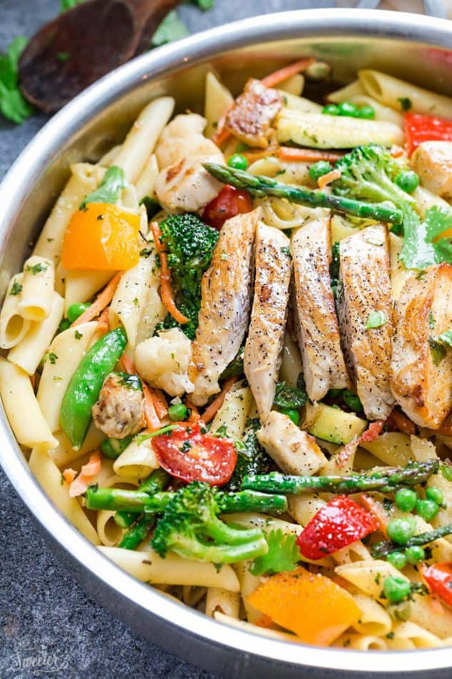 Close-up of pasta primavera topped with sliced chicken in a skillet