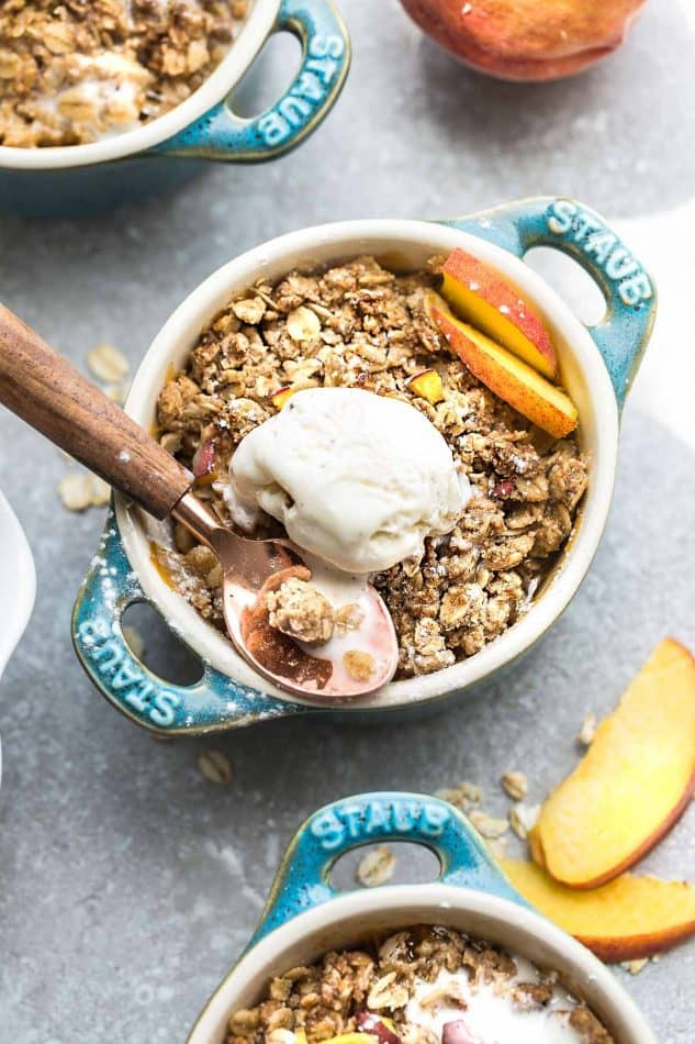 Overhead image of peach crisp in blue bowl with ice cream.