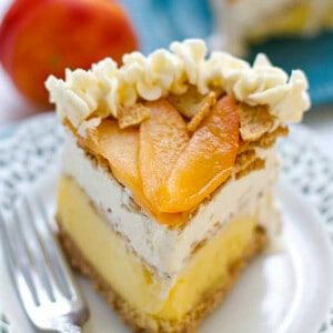 Side shot of one slice of peach ice cream cake on a white plate with a fork
