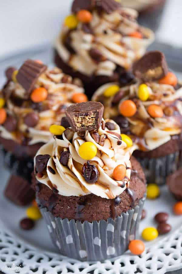 Peanut Butter Chocolate Cupcakes make the perfect decadent treat! Best of all, they come together easily packed with a peanut butter frosting, Reese's pieces, a mini Reese's peanut butter cup and a drizzle of chocolate sauce! So delicious!