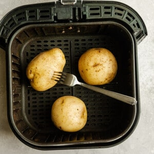 Fork piercing uncooked potatoes in an air fryer basket