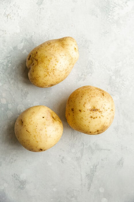 Top view of three raw potatoes on a grey background