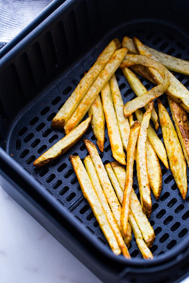 A batch of cooked french fries in an air fryer basket