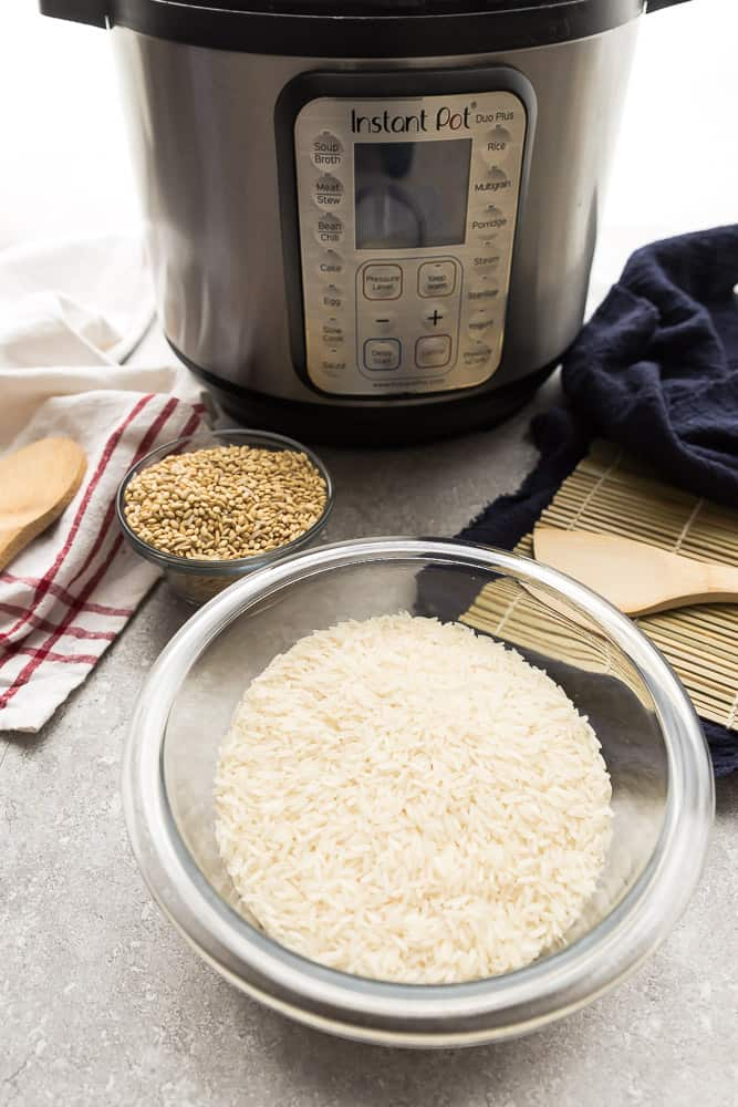 A Glass Bowl Filled with Uncooked White Rice with an Instant Pot in the Background