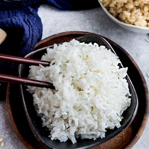 A Pair of Chopsticks Digging Into a Bowl of White Rice