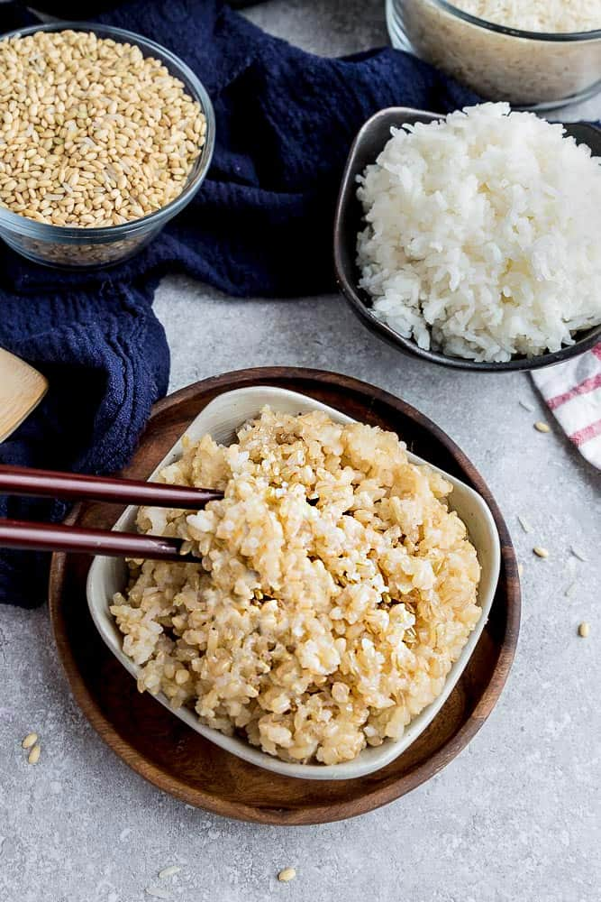 bowl of Instant Pot brown rice in a small white bowl with wooden chopsticks.