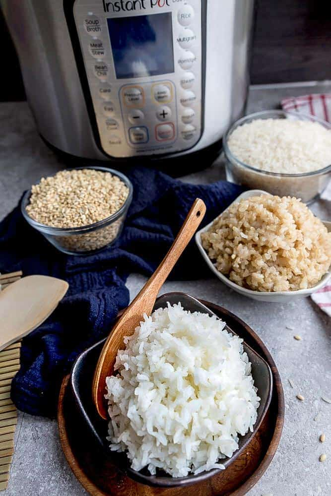 Delicious pressure cooker white rice in a small black bowl with a wooden spoon.