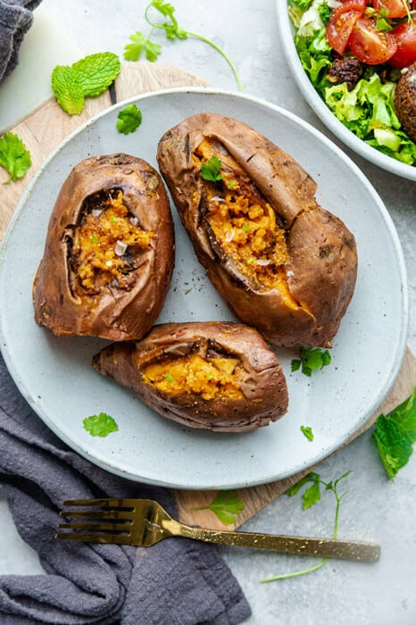 Three Instant Pot baked sweet potatoes with parsley on a white plate