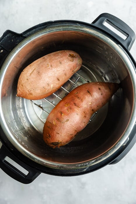 Top view of two raw sweet potatoes in an Instant Pot