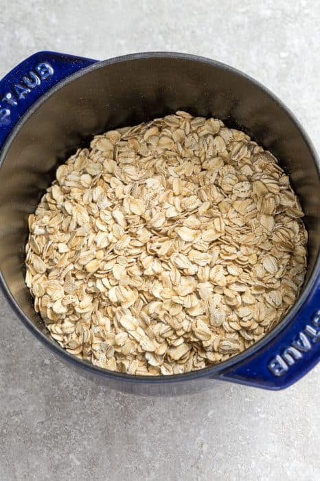 Top view of old fashioned rolled oats in a blue pot on a grey background