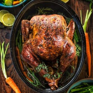 Top view of a perfectly golden brown turkey in a pan with side dishes