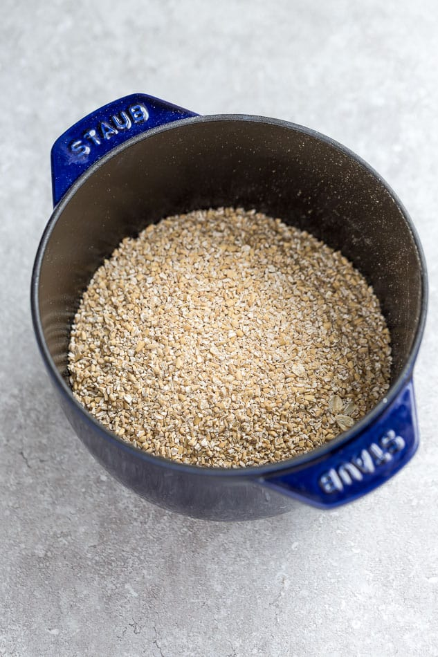 Top view of steel cut oats in a blue pot on a grey background