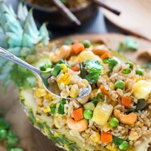 Pineapple Fried Rice served in a hollowed-out half pineapple with a bite on a spoon