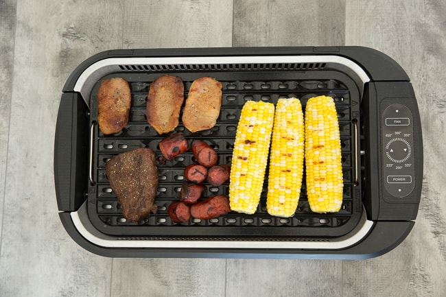 Pork, steak, sausage chunks and ears of corn in a Power Smokeless Grill