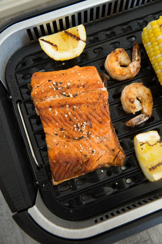 Close-up view of shrimp, salmon, lemon and corn in a Power Smokeless Grill