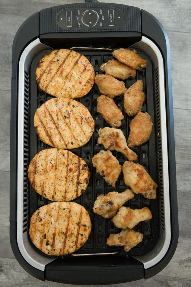 Overhead view of chicken burgers and wings in a Power Smokeless Grill