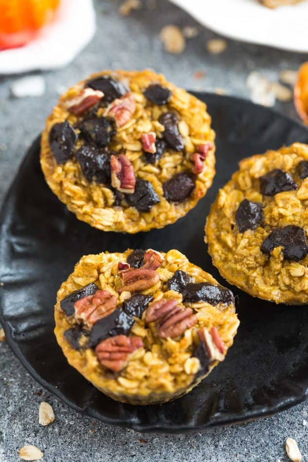 Top view of three healthy Pumpkin Baked Oatmeal Cups on a black plate