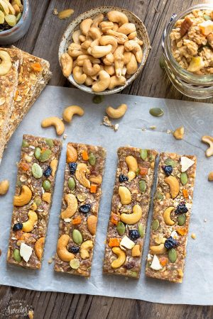 Four No Bake Pumpkin Cashew Granola Bars on parchment paper with a bowl of granola and cashews next to them.