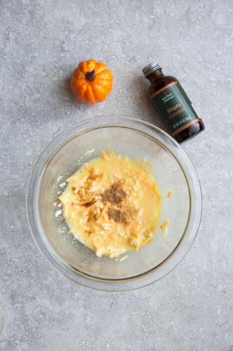 Top view of ingredients to make pumpkin chaffles on a grey background