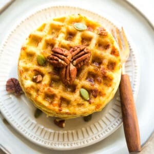 Top far view of pumpkin chaffles on a white plate with pecans, pumpkin seeds and sugar free syrup on a white plate with a fork