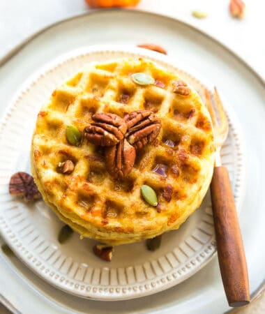 Top view of 3 pumpkin chaffles on a white plate with pecans, pumpkin seeds and sugar free syrup on a white plate with a fork