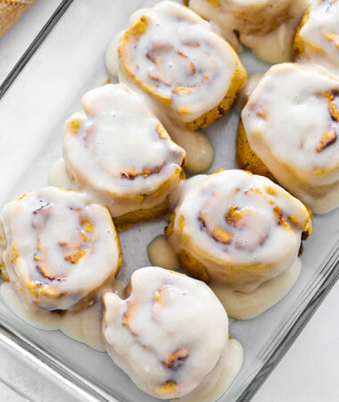 Top view of frosted dairy free pumpkin cinnamon roll dough in a clear casserole dish