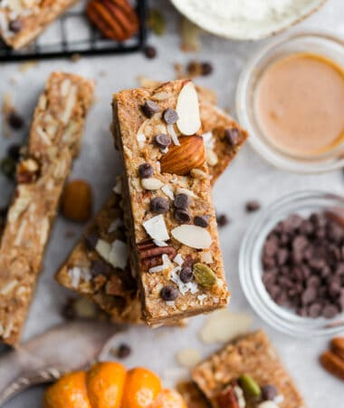 Close up top view of stacked pumpkin granola bars with chocolate chips on a grey background