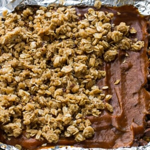 Overhead view of Oatmeal layer being spread over Chocolate Chips and Pumpkin in a foil-lined pan