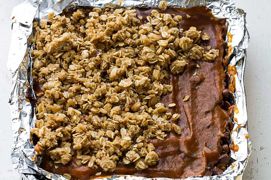 Oatmeal Topping being spread over caramel and chocolate chip layers in a foil-lined pan