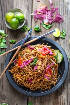 Easy Rainbow Asian Skillet Peanut Noodles in a large black bowl with wooden chopsticks on a wooden table.